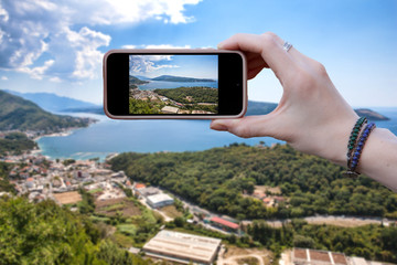 Woman tourist takes pictures on a smartphone beautiful view of the sea and the city in Montenegro. Concepts and technologies of travel.