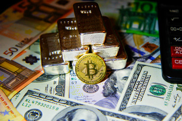 golden bitcoin cryptocurrency against the background of fiat money and precious metals silver