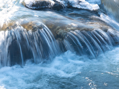 Splashes and drops of water in a small waterfall in winter