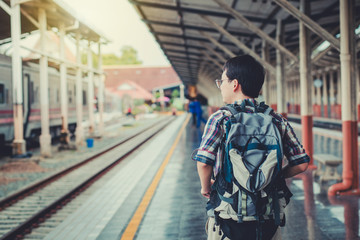 Young man asian with backpack at the train station. Travel concept.