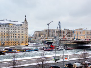 Ships with construction equipment are in Moscow-river under the bridge. Reconstruction of Bolshoy Moskvoretsky Bridge. Winter cloudy day in Moscow, Russia.