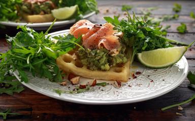 Potato waffles with avocado guacamole and smoked salmon for breakfast