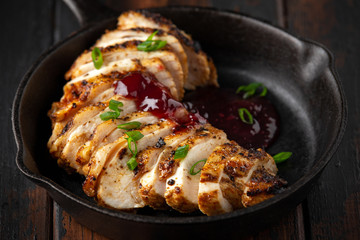 Grilled sliced chicken breast with cranberry sauce in mini cast iron frying pan