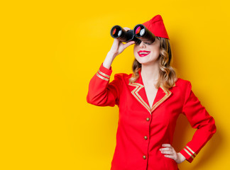 charming vintage stewardess wearing in red uniform with binoculars