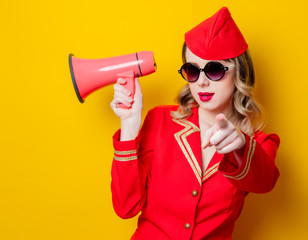 vintage stewardess wearing in red uniform with megaphone