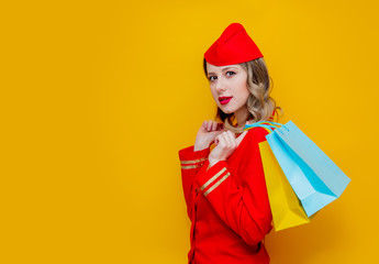stewardess wearing in red uniform with shopping bags.