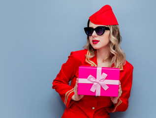 stewardess wearing in red uniform with holiday gift board