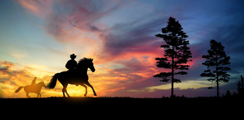 A silhouette of two cowboy and horse at sunset