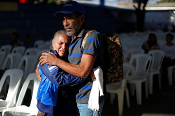 Relatives comfort each other during the wake of 5 relatives of Omar Pimentel, member of the coaching staff of first division soccer team Sonsonate, in Chalchuapa