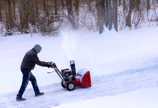 Man using snowblower to clear an uphill driveway