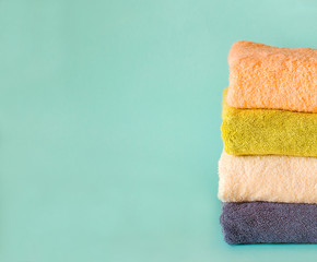 Stack of terry towels on a green background. Laundry day.