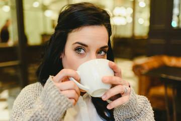 Pretty brunette woman drinking coffee in Vienna, European city, during a trip.