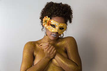 Beautiful Brazilian afro girl ready for the carnival. Golden body painting. Fashion girl with carnival mask.