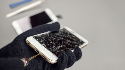 Technician or engineer opening broken smartphone for repair or replace new part on desk with copy space
