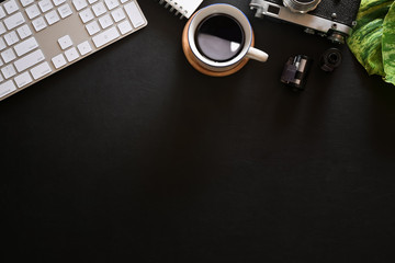 Office leather dark desk table with croissant, coffee, vintage camera, film and copy space