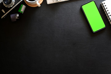 Mockup mobile phone on photographer workplace with leather dark background and copy space