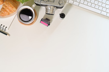 Office wood desk table with vintage camera, coffee, film, creative supplies and copy space
