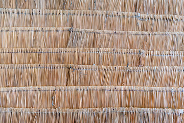 The texture of thatched wicker roof in Asia. Thatch roof background, hay or dry grass.