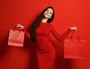 Smiling happy woman in red tight dress holds two red shopping bags