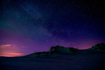 Starry sky at dusk by a mountain
