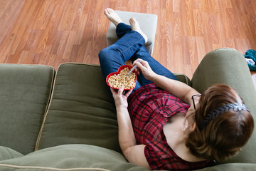 over head view of  woman sitting on couch eating cereal