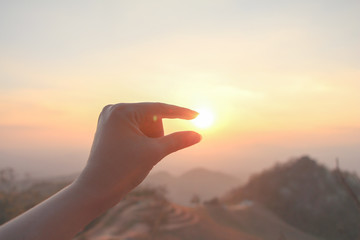 Hand up holding or catch the sun with beautiful nature sunset on mountain with vanilla sky as vacation.