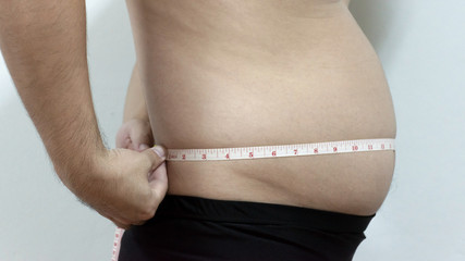Fat man belly. concept of losing weight of people who are obese. holding a measuring tape check out his body.