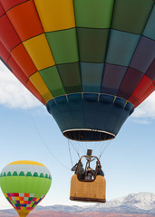 Three people lift off in the basket of a colorful hot air balloon, one woman looks back and takes a picture with her cell phone.