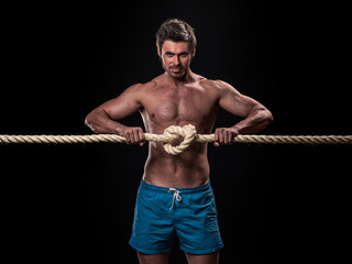 Muscular man with heavy ropes