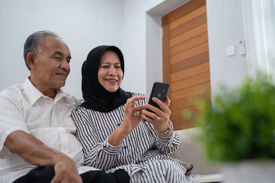 mature asian couple using modern smartphone technology at home together