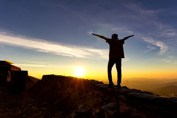 Silhouette of traveler stand exten and raise arms at top of mountain.