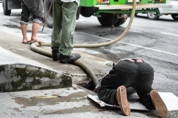 Municipal staff bend into sewerage hatch to rubber band into the city drain, cleaning the drain.