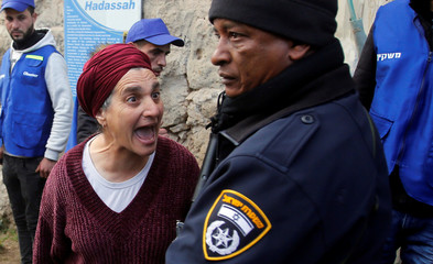 Jewish settler argues with an Israeli policeman during a protest by Palestinians in Hebron, in the Israeli-occupied West Bank