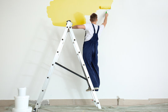 Male painter using roller for refurbishing color of wall indoors