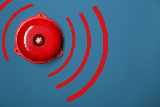 Modern alarm bell on color background