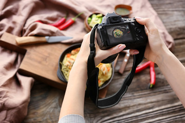 Young woman taking picture of food on wooden table