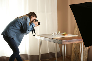 Young woman taking picture of drink in professional studio