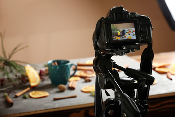 Photo of cup of tea on screen of professional camera in studio