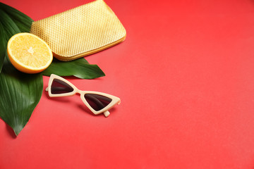 Stylish sunglasses with orange fruit, bag and tropical leaves on color background
