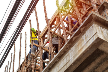 workers working for a new home building with wood scaffolding