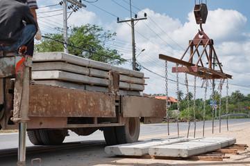 Hoisting construction works with tower crane lifting concrete block, plate, slap, floor sheet, surface.