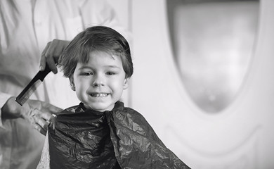 Hairdresser and boy. The boy is doing his hair. Cut hair child in the hairdresser.