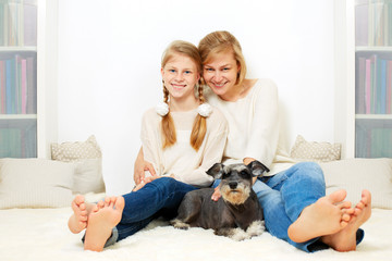 Mother with her 10 years old kid girl sitting home, casual lifestyle photo series. Cozy homely scene.