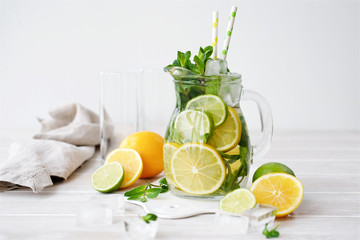 Lemonade in a glass jug on light background. Lemon, Mint, Lime and Ice Ingredients
