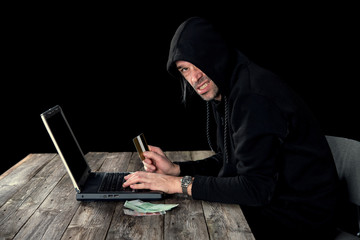Fototapeta hacker in black hoody with laptop, bank card and euro notes