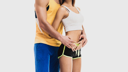 part of young healthy sporty couple huging on white background
