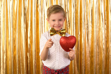 Valentine's Day. Smiling blond boy, 6 years old, holding a big red heart. Golden studio background.
