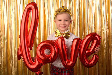 Valentine's Day. Smiling blond boy, 6 years old, holding a big red letters love. Golden studio background.