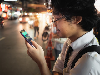 Young Asian business man using mobile smart phone in the street at night. Social and internet of thing concept.