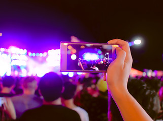 Hands of unidentified taking a photo with mobile smart phone of concert stage.